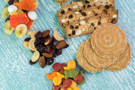 Close up of variety of snacks: tropical nut trail mix, goldfish crackers, granola bars and almond biscuits - delicious snacks on a blue wooden background.