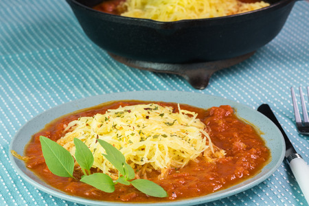 marinara sauce: Close up of plate with rosted spaghetti squash and marinara sauce on a table.