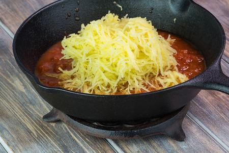 Close up of roasted spaghetti squash with marinara sauce in iron pan.