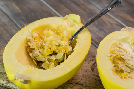 Close up of halves of  spaghetti squash and spoon for removing seeds. Stock Photo