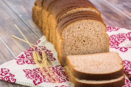 whole wheat bread: Close up of cut whole wheat bread on a wooden background. Stock Photo