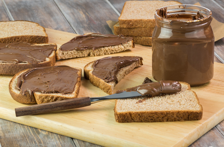 Chocolate spread in jar and pieces of bread with chocolate spread.
