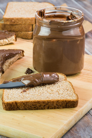 Chocolate spread in jar and pieces of bread with chocolate spread on a cutting board.