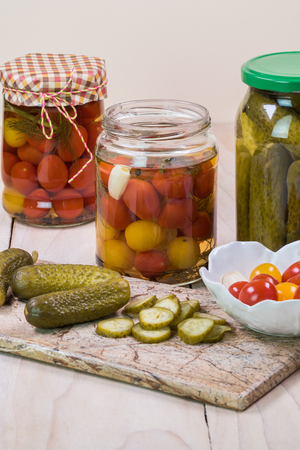 Close up of  pickled vegetables in glass jars and pickles on a cutting board.