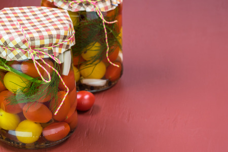 Close up of glass jars of cherry tomatoes pickles with lid.