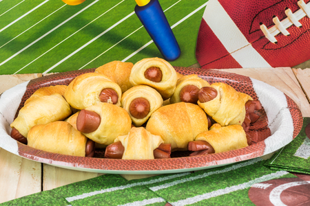 decotated: Close up of plate with pigs in blanket on the table decotated for football game party.