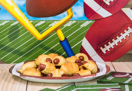 Close up of plate with pigs in blanket on the table decotated for football game party.