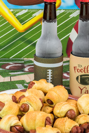 Close up of bottles of beer and plate with pigs in blanket on the table decotated for football game party.