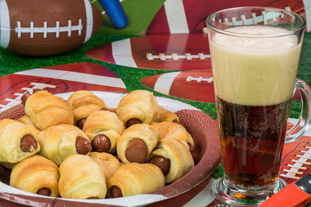 Close up of glass of beer and plate with pigs in blanket on the table decotated for football game party. Archivio Fotografico
