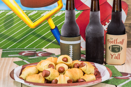 Close up of bottles of beer and plate with pigs in blanket on the table decotated for football game party. Stok Fotoğraf - 61792597