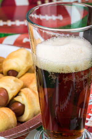 Close up of glass of beer and plate with pigs in blanket on the table decotated for football game party. Stock Photo