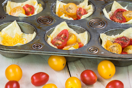 Close up of muffin pan with unbaked tomato cheese tarts and cherry tomatoes.