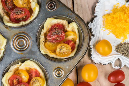 shredded cheese: Close up of muffin pan with unbaked tomato cheese tarts and bowl with shredded cheese. Stock Photo