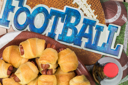 Top view of bottle of beer and plate with pigs in blanket on the table decotated for football game party.
