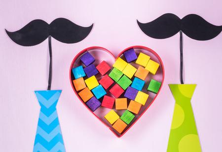 Homohuwelijk. Symbolen twee snorren en banden met regenboog gekleurde houten stukken in metaalvormig hart.