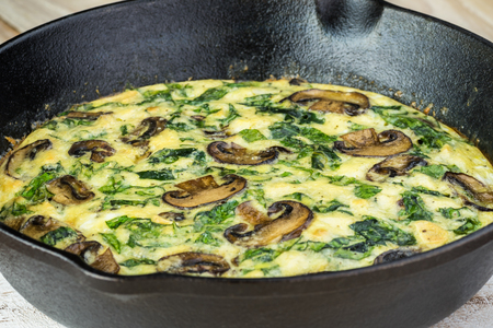 Close up of iron skillet with spinach mushroom frittata.