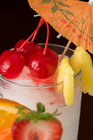 colada: Close up of glass of frozen pina colada cocktail garnished with cherry and pieces of pineapple. Stock Photo