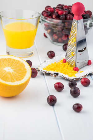Close up of ingredients: cranberries, orange, orange zest for cranberry orange sauce.
