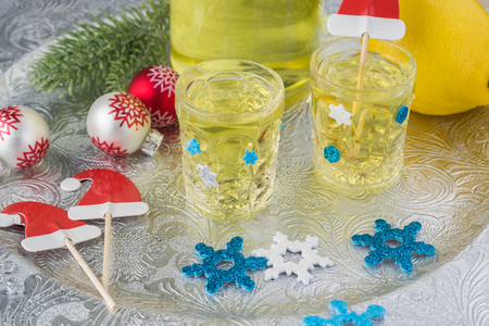 Close up of glasses with homemade limoncello on a silver plate decorated for holiday.