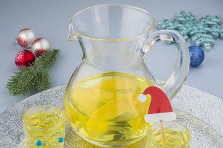 Close up of pitcher and glasses with homemade limoncello on a silver plate decorated for holiday.