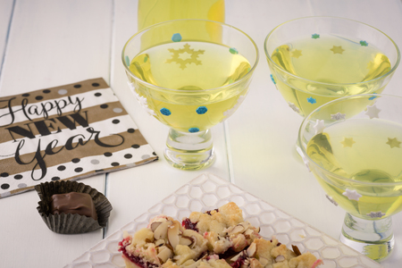 Close up of glasses with homemade limoncello on a table decorated for New Year party.