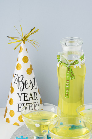 Close up of glasses and bottle with homemade limoncello decorated for New Year party.