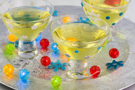 Close up of glasses with homemade limoncello on a silver plate decorated for New Year party.