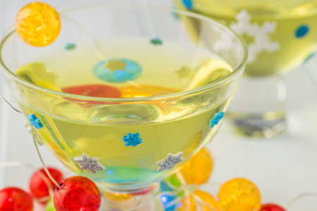 Close up of glass with homemade limoncello  decorated with lights for New Year party.