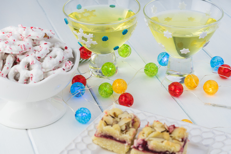 Close up of glasses with homemade limoncello on a table decorated with lights for New Year party. Stock Photo