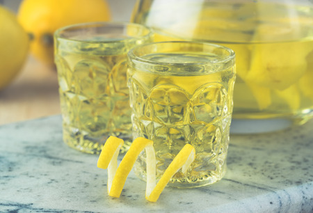 Close up of pitcher and glasses with homemade limoncello. Stock Photo