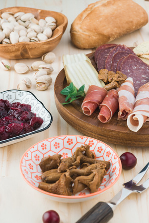 Top view of plate with sliced salami, prosciutto, crackers, green olives. Stock Photo