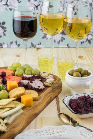 Close up of cutting board with assorted cheese and glasses with wine and limoncello.