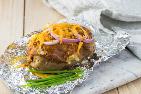 Close up of  loaded baked potatoes with  chili, onion, cheese. Stock Photo
