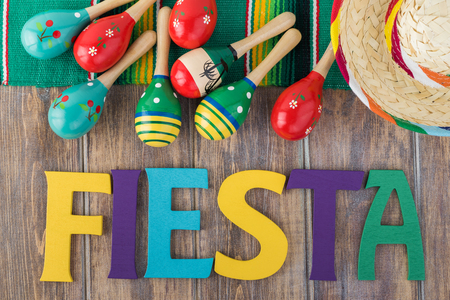 Top view of fiesta table decoration with colorful  letters and  maracas on a wooden background.