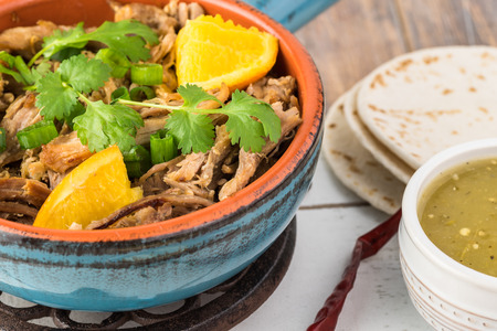 Close up of table with slow cooked pork carnitas and salsa verde. Stock Photo