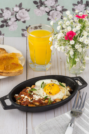Close up of shirred egg with marinara and feta in individual cast iron on a kitchen table. Banque d'images