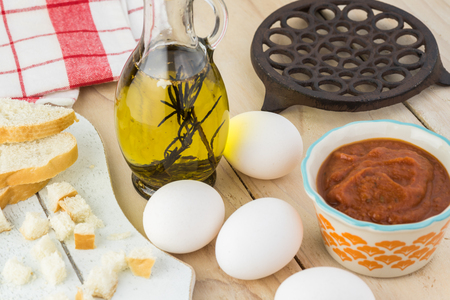 Close up of eggs, marinara sauce, cut cubes of bread - ingredients for shirred eggs with marinara and feta. Imagens