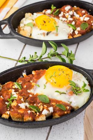 marinara sauce: Close up of shirred eggs with marinara and feta in individual cast iron.
