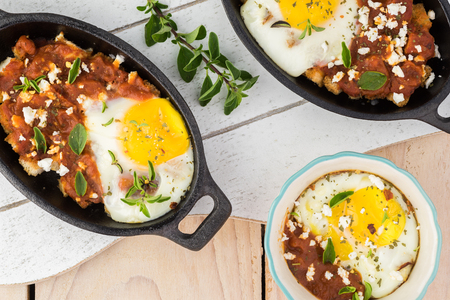 Top view of shirred eggs with marinara and feta in individual cast iron. Standard-Bild