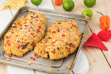 Close up of cutting board with fillets of tilapia coated with tortilla, chipotle and lime crust. Фото со стока