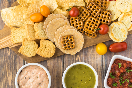 Top view of cutting board with variety of snacks and bowls with dip and salsa.