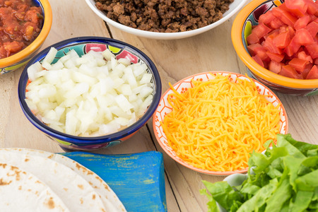 Close up of table with ingredients for beef tacos -  tortillas, ground beef, cut onion, shreded cheese. Stock Photo