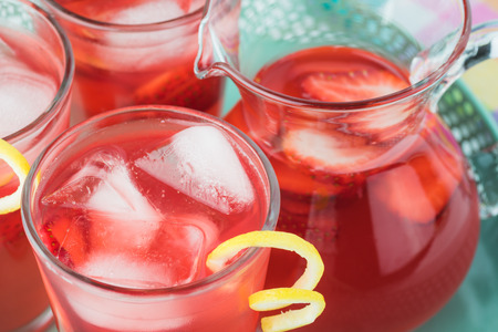 Close up of  tray with glasses and pitcher of strawberry rhubarb lemonade.