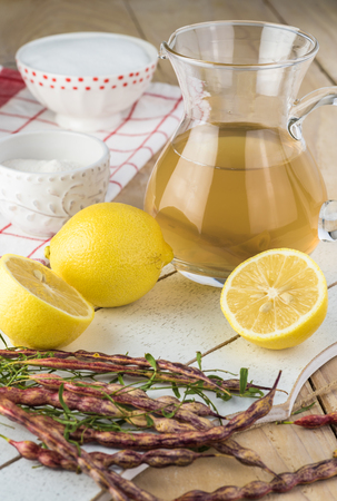 Close up of pitcher with mesquite bean tea, sugar, lemon, pectin -  ingredients for mesquite bean jelly. Stock Photo