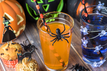 Glasses of beverage  decorated for Halloween party with spiders and ghost lights. Imagens
