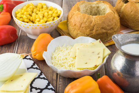 Close up of ingredients for corn and cheese chowder in bread bowl - bell peppers, sweet corn, onion, cheese. Stock Photo