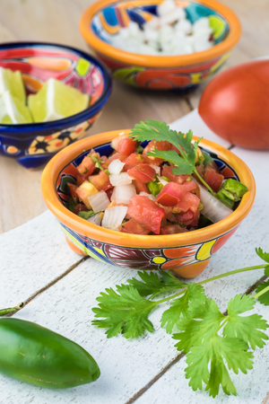 gallo: Close up of bowl with chunky salsa pico de galla and ingredients.