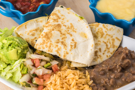 gallo: Close up of plate with spinach mushroom quesadillas with refried beans and rice. Stock Photo