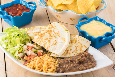Close up of plate with spinach mushroom quesadillas with refried beans and rice. Stock Photo