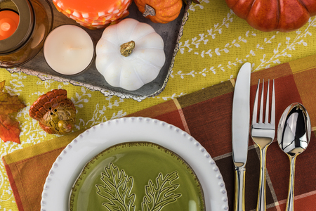 Top view of table set with colorful plates, silverware and center piece arrangement for Thanksgiving party.